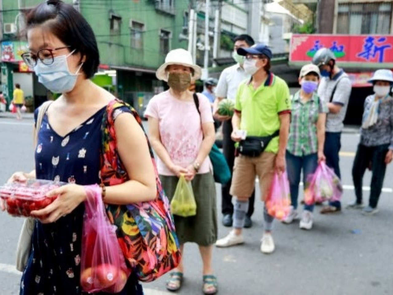 People wearing face masks shop for necessities. Photo: AFP