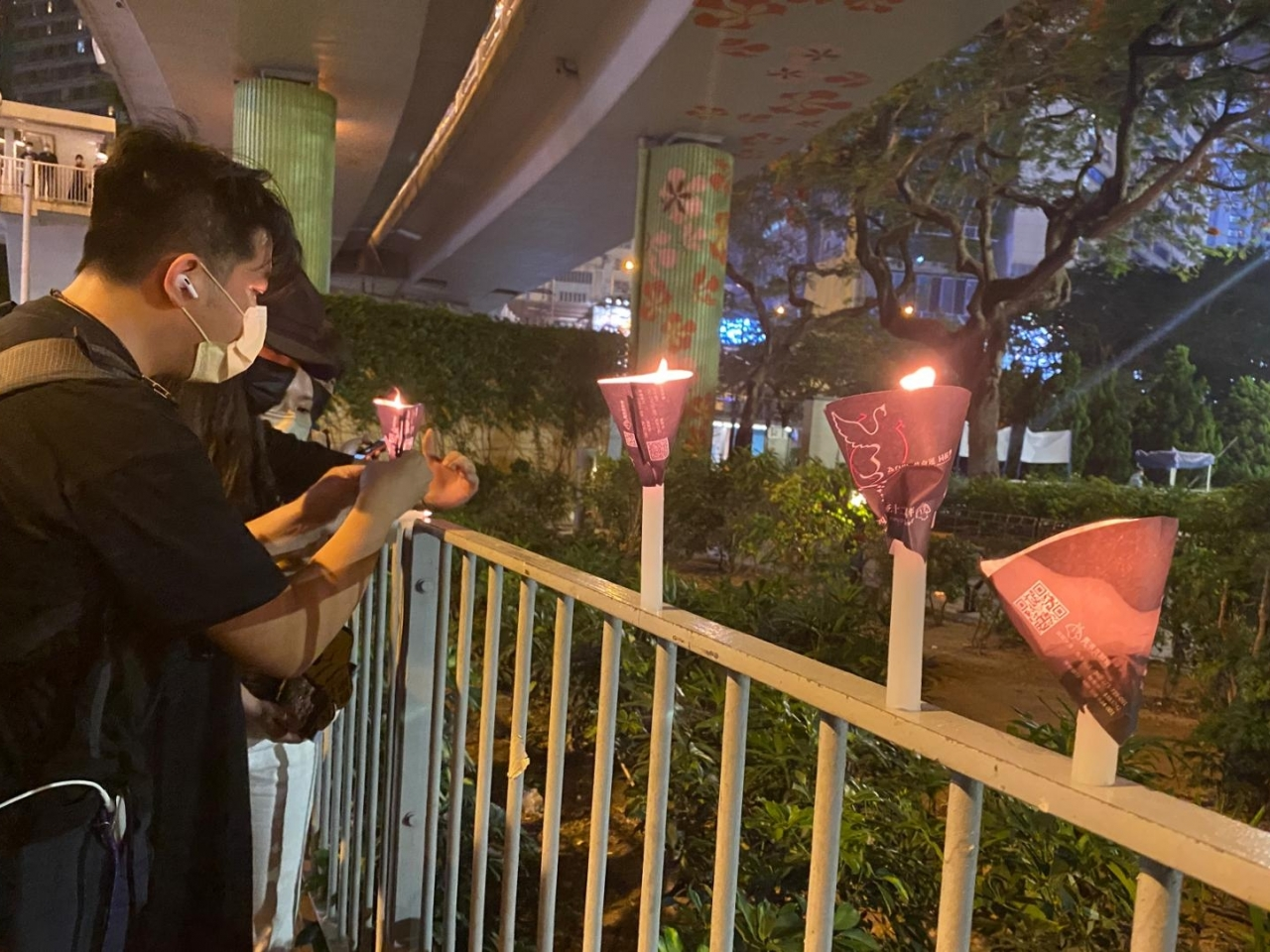 Mourners of the 1989 crackdown in Beijing lit candles around Victoria Park before police usher them away. Photo: RTHK