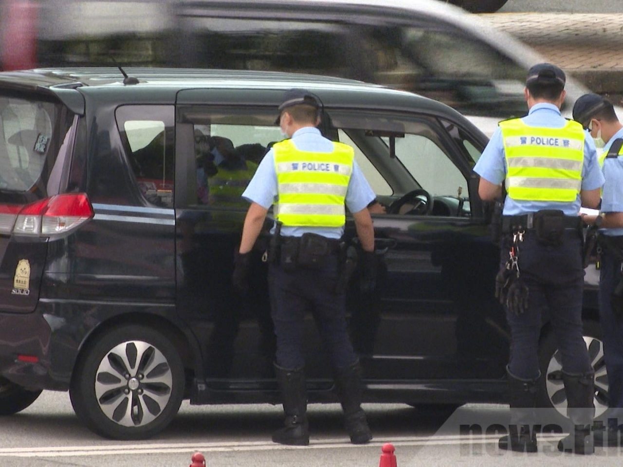 Police officers stop a vehicle at the Cross Harbour Tunnel in Hung Hom. Photo: RTHK