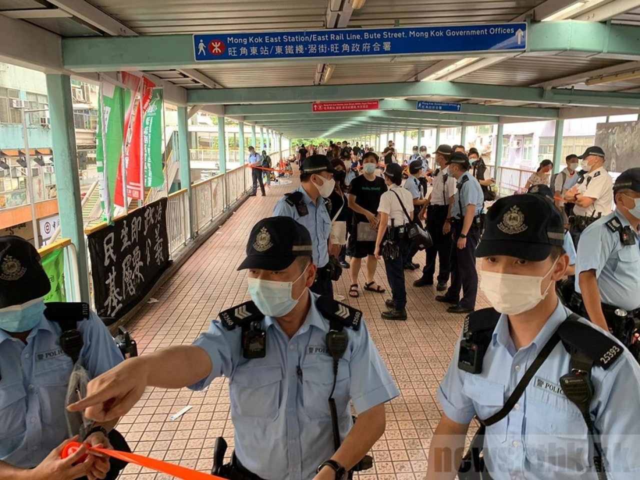 Police officers surround booths by the Confederation of Trade Unions in Mong Kok. Photo: RTHK