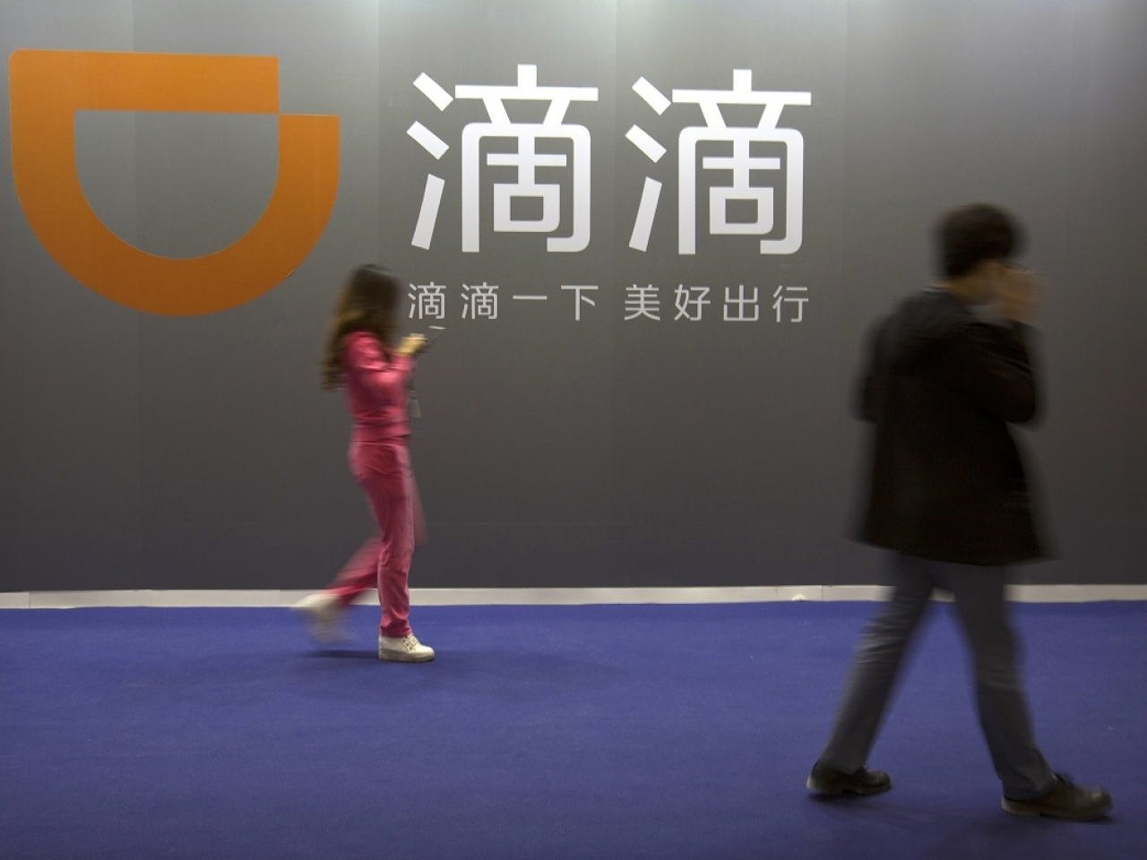A member of the public walks past a sign for Didi Chuxing. File photo: AP