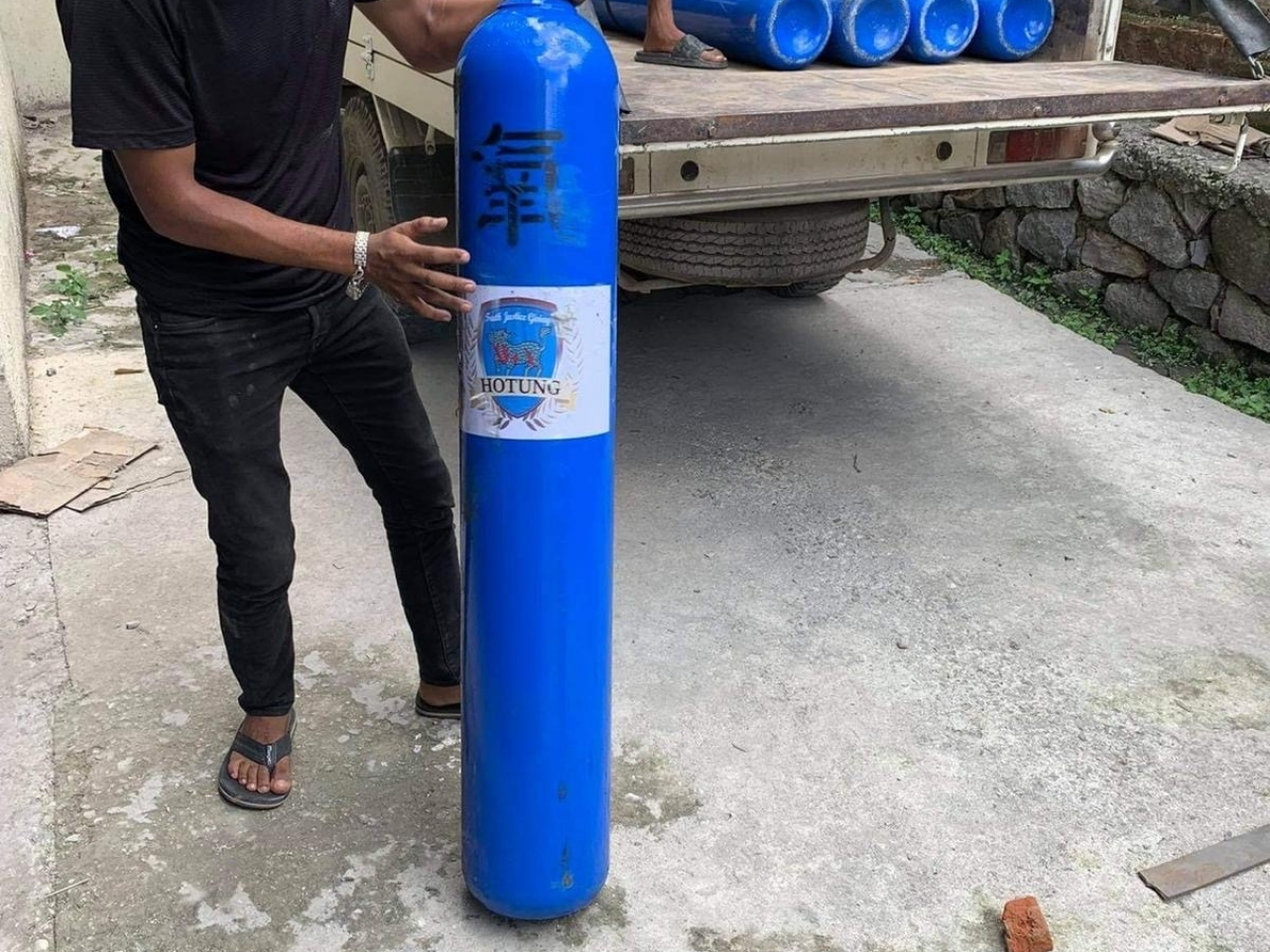 A Nepalese porter helps to reload oxygen cylinders onto a truck after the had to be carried by hand around a landslide. Photo: submitted
