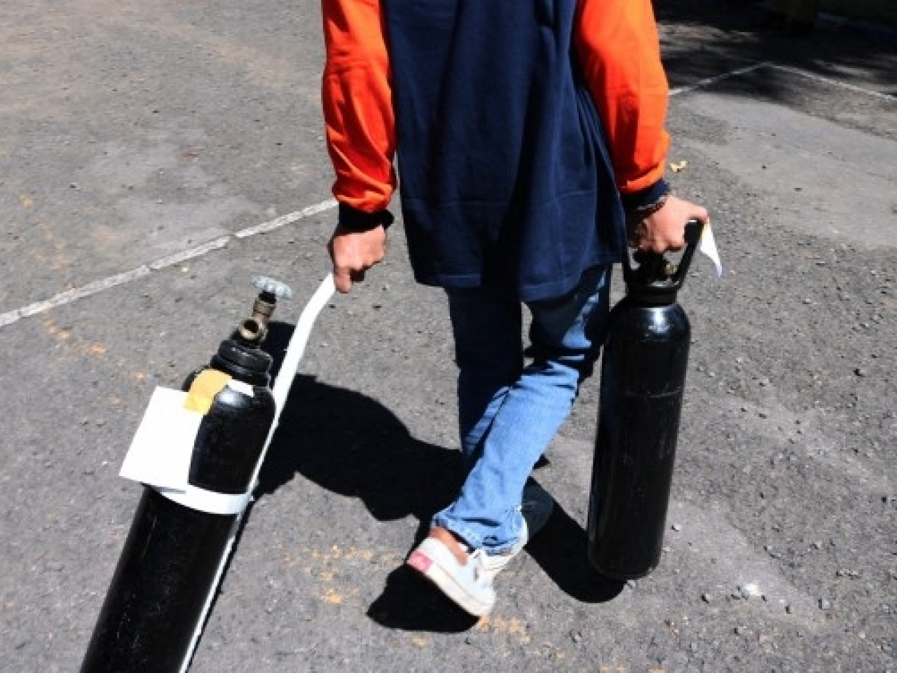 Workers handle free charging oxygen cylinders for residents exposed to Covid-19. Photo: AFP
