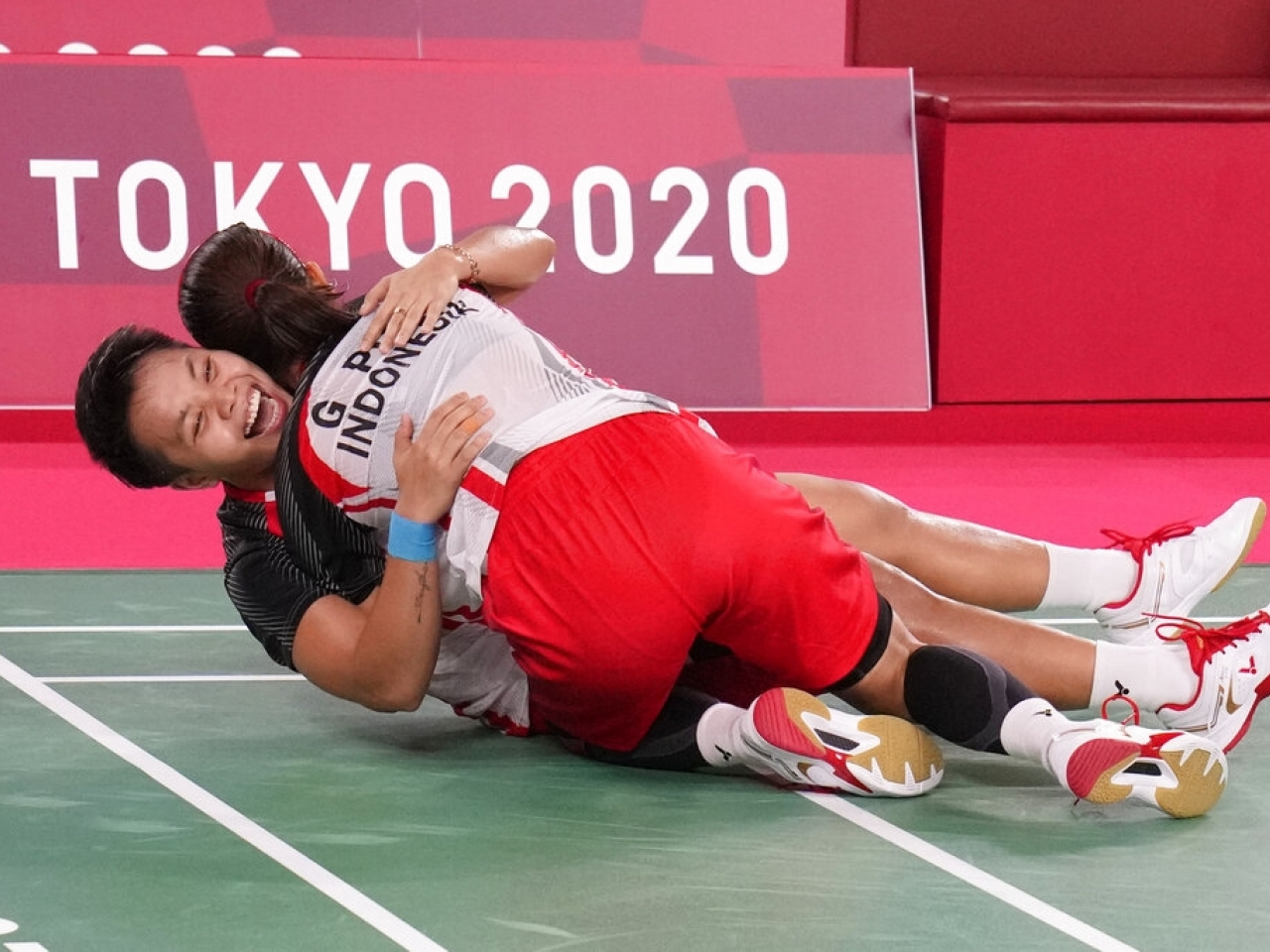 Apriyani Rahayu, left, and Greysia Polii celebrate their victory over their Chinese opponents in the badminton women's doubles final. Photo: AP