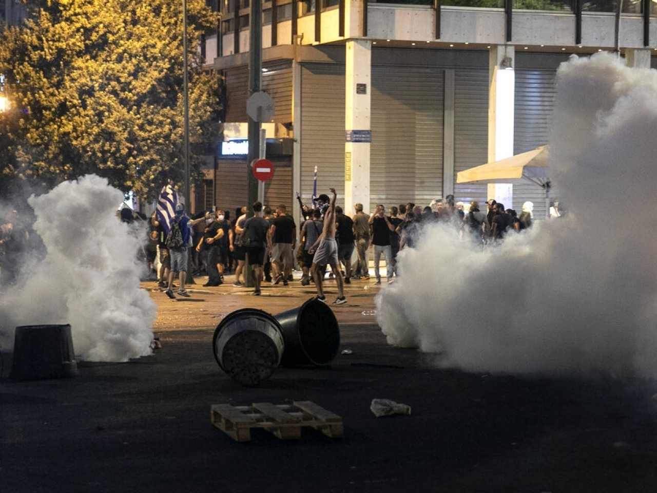 Anti-vaccine protesters run to avoid tear gas during clashes at central Syntagma square, in Athens. Photo: AP