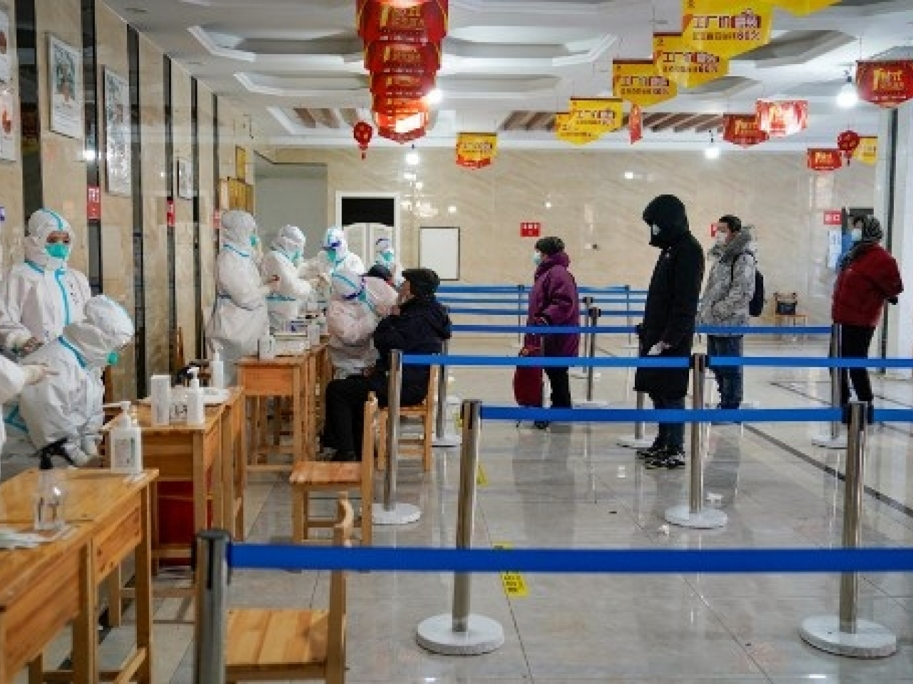 A medical worker takes a swab sample from a man to test for Covid-19 coronavirus at an office building in Harbin. Photo: AFP