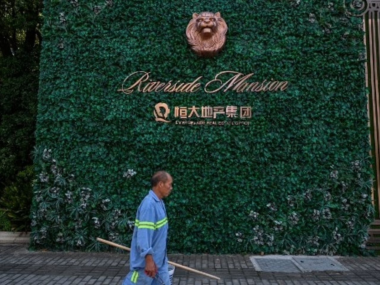 A man walks past a residential building developed by Evergrande in the Pudong district in Shanghai. Photo: AFP